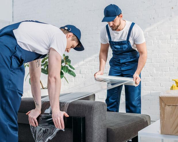 Zwei Umzugshelfer verpacken ein Sofa mit Stretchfolie um es vor Verschmutzungen, Feuchtigkeit und Beschädigungen zu schützen