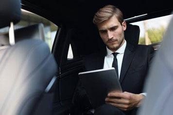 Geschäftsmann sitzt im Taxi und bedient sein Tablet