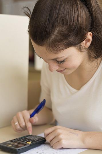 Mädchen rechnet mit einem Taschenrechner in der Schule