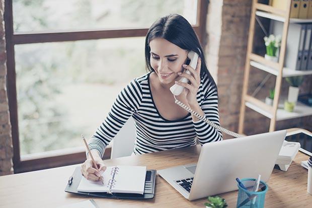 Frau telefoniert an ihrem Arbeitsplatz und macht sich Notizen in einem Kalender
