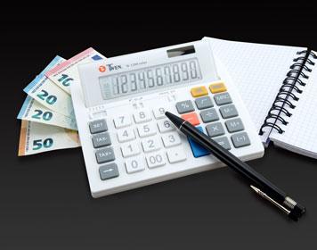 Tischrechner mit Geldscheinen und Notizbuch