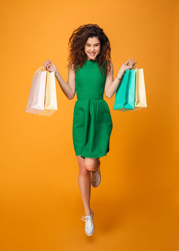 Model in grünem Kleid mit vielen verschiedenfarbigen Tragetasche in den Händen springt vor orangefarbenem Hintergrund in die Höhe