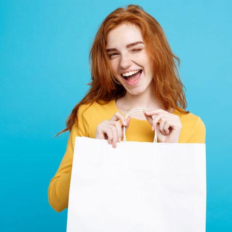 Model in geben Langarmshirt mit weißer Tasche vor cyanfarbenem Hintergrund zwinkert in die Kamera