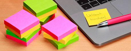 Verschieden farbige Postits-Stapel liegen neben einem Laptop