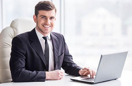 Ein Mann mit Anzug sitzt an einem Notebook