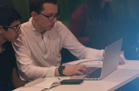 Zwei Jungs gucken auf den Bildschirm eines Notebooks